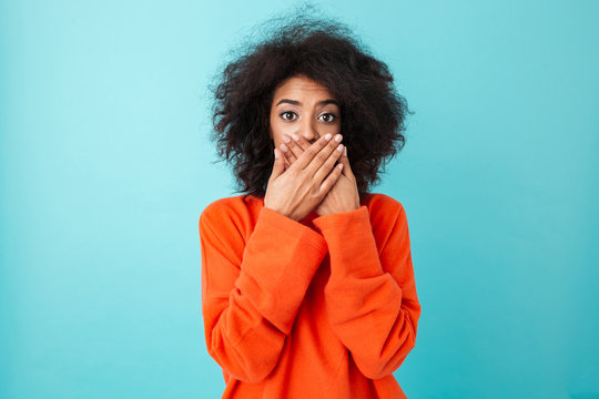 Image of shocked woman 20s in casual clothing looking on camera and covering open mouth with hands, isolated over blue background