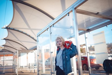 Woman holding skateboard at bus stop