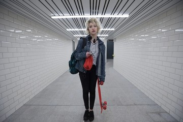 Woman standing with skateboard in subway