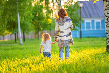 Mother and little daughter walking in spring sunny park