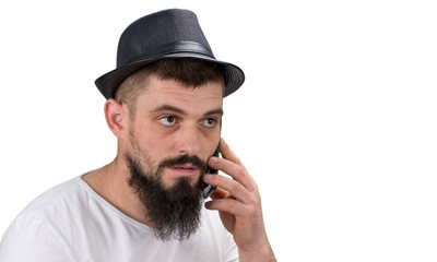 Serous bearded  man in hat  talking on the phone isolated on white background with copy space