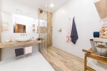 Modern interior of the bathroom. The shower compartment is covered with tiles in the color of wood, white walls and a white floor and a washbasin with a large mirror