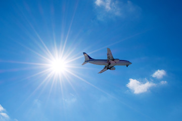 Passenger airplane flies in a blue sky with a bright sun.