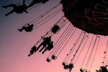 silhouettes of people on swing carousel against purple evening summer sky