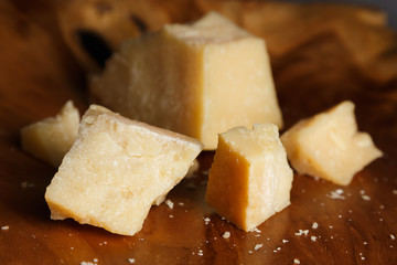 Parmesan cheese on a wooden board. Pieces of cheese close-up.