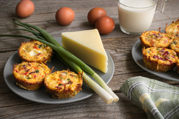 Muffins with scrambled eggs, cheese, bacon, potato and red pepper. Breakfast concept. Gray, rustic wooden background.
