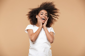 Portrait of a shocked young african woman celebrating