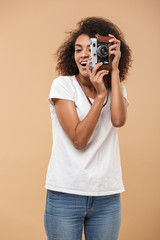 Portrait of a smiling young african woman taking photo