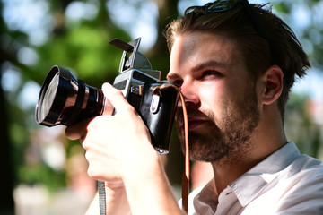 Man with beard holds photocamera on green nature background