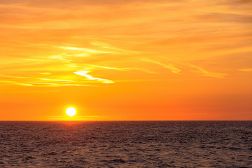 Beautiful round and bright sun setting against a vivid orange sky with high altitude tin clouds over the horizon of the North sea