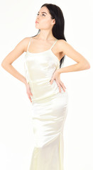 Lady on calm face wears expensive fashionable evening dress. Slim and fit concept. Fashion model with slim figure as result of dieting and fitness. Woman in elegant white dress, white background.