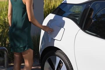 Woman charging electric car at charging station