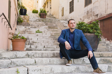The thoughtful man sits on steps of the narrow street