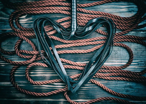 Scourge for BDSM in the form of a heart and a rope for binding on a dark background. Accesories for sexual games.