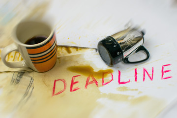Deadline written on paper, a spilled coffee cup and a mechanical timer.