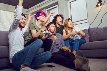 A group of friends playing video games sitting on the couch, laughing in the room.