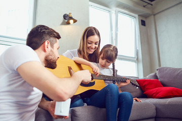The family plays guitar together and sings songs. Mother, father and daughter spend time together.