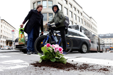 Brussels resident Anton Schuurmans talks to a cyclist after planting flowers in an unrepaired pothole to draw attention to the bad state of public roads in Brussels