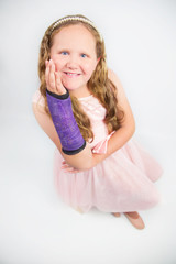 Ballerina in pink with broken arm in purple cast