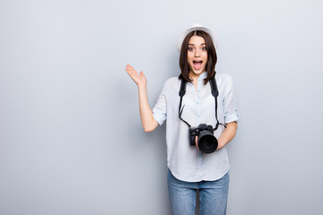 Portrait of positive, confident, pretty, funny, comic, astonished, surprised, stylish girl in casual outfit having using digital camera, wearing jeans, pants, shirt, standing over grey background