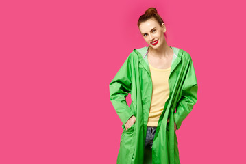 Young woman in a green coat on a pink background.  Colour obsession concept.  Minimalistic style. Stylish Trendy