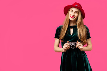 woman on a pink background in a green dress and hat holds a rarity camera in her hands and smiles. Concept of healthy nutrition and sports.  Colour obsession concept.