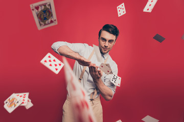 Professional, cunning joyful magician, illusionist, gambler with tricky glance in casual outfit, glasses, throwing, sending cards to the camera, standing over red background