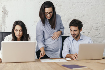 Young pregnant woman at work with his associates in the office while tells them what to do