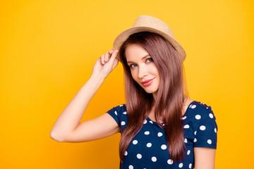 Portrait of sexy, adorable, nice, kind, pretty, lovely, professional woman, tour operator in polka-dot t-shirt holding hand on hat, looking at camera, isolated on yellow background