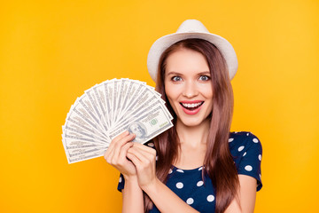It is my dream! Close up portrait of happy cheerful lucky girl holding money fan in hands near face, having white hat on head, isolated on yellow background