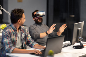 augmented reality and technology concept - developers with singapore city on virtual headset or 3d glasses screen working late at night office