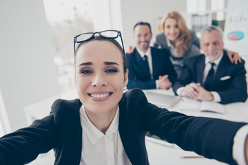 Charming, cheerful, stylish woman having glasses on head shooting self portrait with two hands with her colleagues on blurred background, sitting in workplace, workstation having timeout, pause