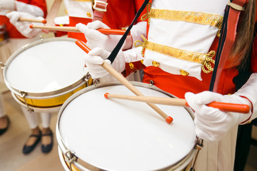 Young girls drummers hands in red uniforms and white skirt with white gloves drumming on drums at marching band