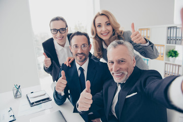 Stylish, attractive agents, experts in formal wear, suits, wearing glasses, spectacles shooting self portrait showing thumb up with fingers, looking at camera, sitting in work place, station at desk