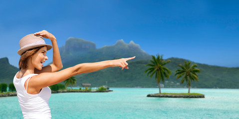 summer holidays, travel, people and vacation concept - happy young woman in hat pointing finger at touristic resort over exotic bora bora island beach background