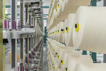 white textile yarn on the warping machine. machinery and equipment in a textile factory