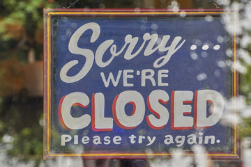 sign in shop window saying Sorry we're closed