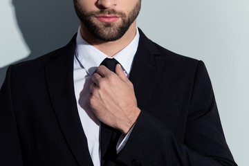 Close up cropped portrait of half face serious man in classy outfit with bristle, holding hand on tie, preparing for event, isolated on grey background