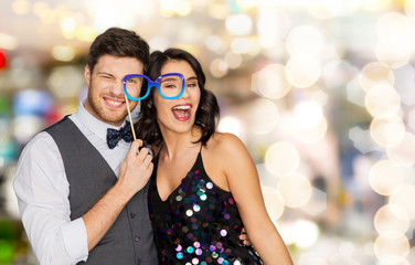 celebration, fun and holidays concept - happy couple posing with party glasses over lights background