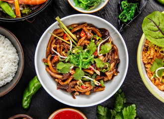 Asian udon noodles with spicy soy sauce and chicken pieces, top view