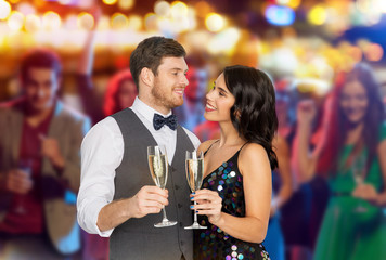 celebration and holidays concept - happy couple with glasses drinking non alcoholic champagne at party over night club lights background