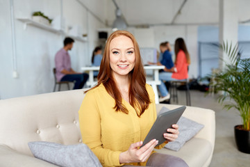 business, education, technology and people concept - smiling young redhead woman with tablet pc computer working at office