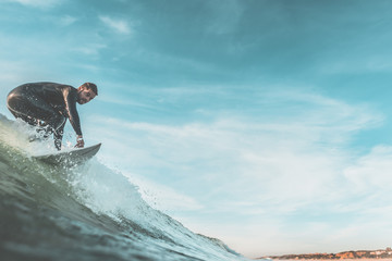 Man catching an ocean wave near the coast. Extreme water sports and outdoor active lifestyle. Vintage filter with soft style. With copy space for text.