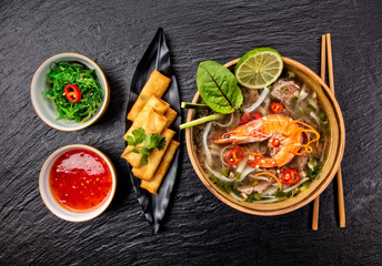 Asian shrimps soup with spring rolls and chopsticks.