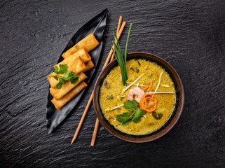 Asian kari soup with spring rolls and chopsticks.