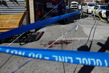 Blood is seen on the sidewalk at the crime scene where New York police officers shot to death an unarmed black man who pointed a metal pipe at them, in the Crown Heights section of Brooklyn, New York