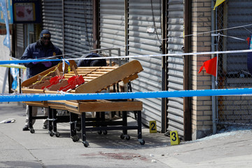 NYPD crime scene investigators work the scene where New York police officers shot to death an unarmed black man who pointed a metal pipe at them, in the Crown Heights section of Brooklyn, New York