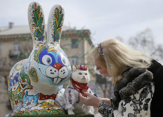 A woman dresses her cat before taking pictures near a painted Easter Bunny, displayed in a square as part of the upcoming Orthodox Easter celebration, in Kiev