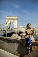 Young woman using mobile phone with Chain bridge at background in Budapest