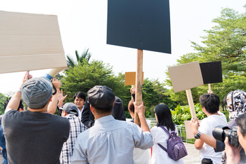 The youth crowd Men and women share a protest sign hold a megaphone. Mob, the gathered to Protest gather claim to solve the problem include pollution, energy, labor, human women right, promotion sale.